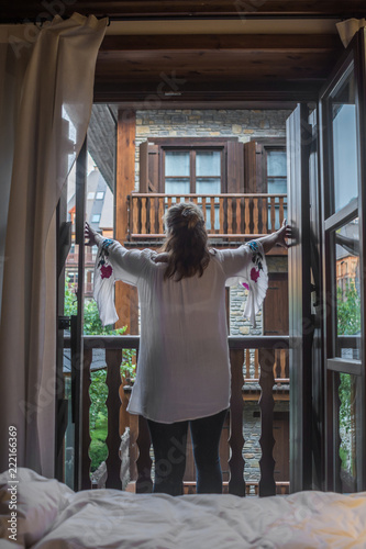 Woman on the balcony of her room enjoying a sunny day - 222166369