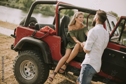 Poster Young woman and man having fun outdoor near car