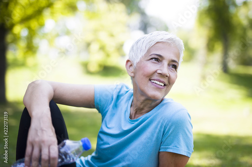 Wall mural Portrait of smiling senior woman relaxing after exercising