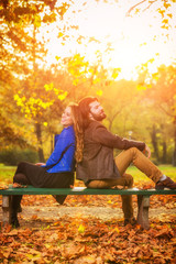 Couple in autumn season colored park enjoying outdoors.
