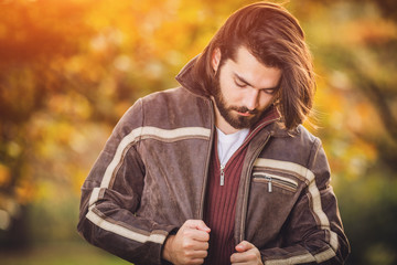 Handsome young man wearing leather jacket in autumn season / cold weather.