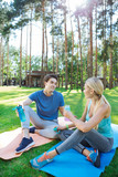 After a workout. Positive joyful people sitting on yoga mats while talking to each other - 222189502