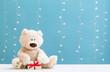 Leinwanddruck Bild - A teddy bear and gift box on a shiny light blue background