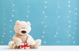 A teddy bear and gift box on a shiny light blue background