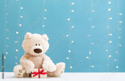 Leinwanddruck Bild A teddy bear and gift box on a shiny light blue background