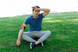 After workout. Nice tired man sitting on the green grass while being tired from the workout - 222197363