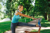 Developing flexibility. Cheerful nice woman smiling while trying to reach her toes