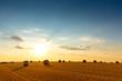 Leinwanddruck Bild - Sonnenuntergang mit Strohballen auf dem Stoppelfeld