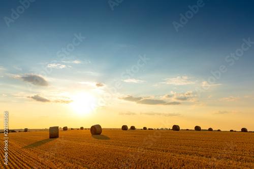 Leinwanddruck Bild Sonnenuntergang mit Strohballen auf dem Stoppelfeld