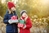Adorable little girls holding a pile of Christmas gifts on beautiful sunny winter day. - 222206141