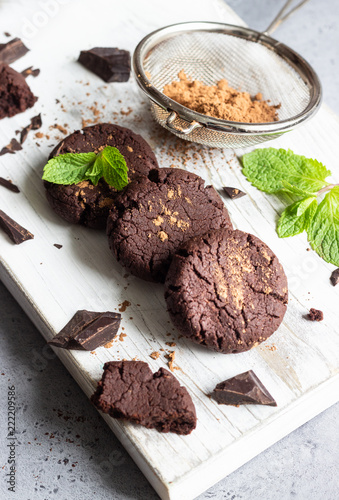 Poster Chocolate cookies, pieces of chocolate, mint and cocoa powder on a white wooden cutting board.