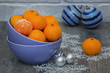 Mandarins and blue decorative balls on gray wooden background.