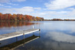 Minnesota lake and dock with trees in full autumn color, blue sky and clouds