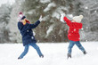 Two adorable little girls having fun together in beautiful winter park. Beautiful sisters playing in a snow.