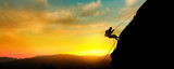 Silhouette of a beautiful athletic woman climbing a steep rock