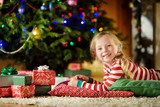 Happy little girl wearing Christmas pajamas playing by a fireplace in a cozy dark living room on Christmas eve. - 222212555