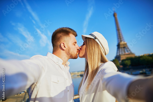 Leinwanddruck Bild Romantic couple taking selfie near the Eiffel tower