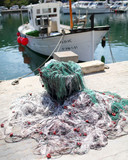 Fishing nets on harbour wall and fishing boat in the Mediterranean - 222216348