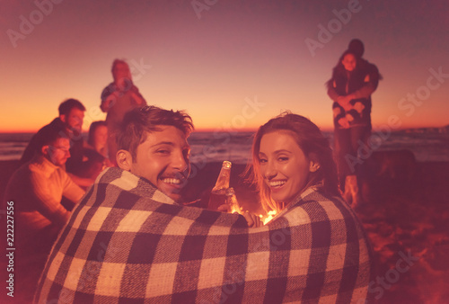 Foto Murales Couple enjoying with friends at sunset on the beach