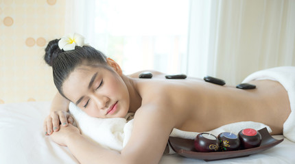 beautiful and healthy young woman relaxing with back stone therapy massage in spa salon © suphaporn