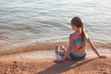 Blonde cute seven year old girl sitting on the beach during vacation
