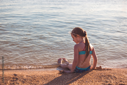 Foto Murales Blonde cute seven year old girl sitting on the beach during vacation