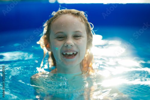 Leinwanddruck Bild Smiling adorable seven years old girl playing and having fun in inflatable pool