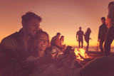 Couple enjoying bonfire with friends on beach