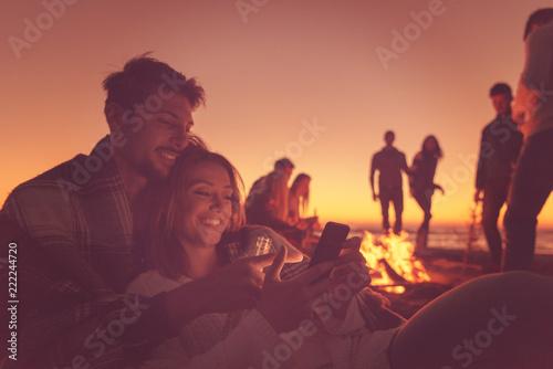 Leinwanddruck Bild Couple enjoying bonfire with friends on beach