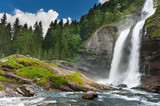 Alpine waterfall in mountain forest under blue sky