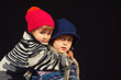 children in warm knitted hats on a dark background . Brother and sister in warm sweaters