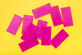 Pink plastic flat rectangles are scattered chaotically on a yellow background. Top View - 222249165