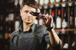 Quadro Bokal of red wine on background, male sommelier appreciating drink