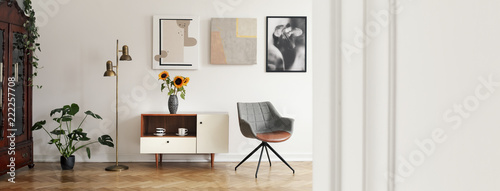 Leinwanddruck Bild Panorama of posters and grey armchair in bright living room interior with copy space. Real photo