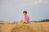 Cute preschool boy, sitting on hastack in field on a cloudy day - 222258734
