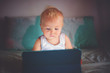 Leinwanddruck Bild - Little baby boy, playing on tablet at home