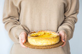 Lemon tart in the hands of a woman in a warm autumn sweater. Home baking concept - 222261362