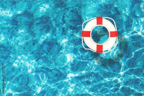 Leinwanddruck Bild Life preserver floating in a clear pool water