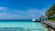Luxury island in Maldives, wooden jetty into blue tropical sea. Blue sky, sunny day in Maldives resort.