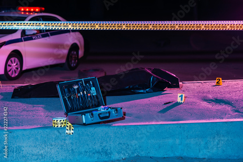 toned picture of case with investigation tools, cross line, police car and corpse in body bag at crime scene - 222274342