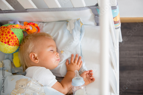 Cute little baby boy, sleeping with bottle with formula milk - 222276967