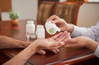 Crop shot of doctor putting pills in hand of senior man sitting at table