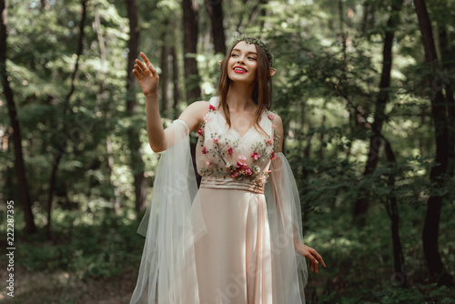 happy elf girl in elegant dress with flowers in woods - 222287395