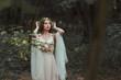 fantasy girl with elf ears in flower dress posing in forest