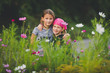 Portrait of two young girls in wild flower meadow looking at camera