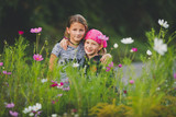 Portrait of two young girls in wild flower meadow looking at camera - 222292967