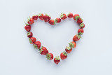 top view of heart shape sign made of fresh strawberries on white surface - 222296378