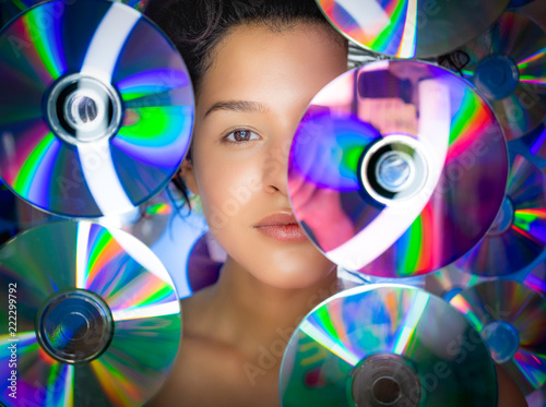 Leinwanddruck Bild Portrait of beautiful woman among CDs