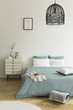 Leinwanddruck Bild - A double bed with sage green and white bedding standing on a wooden floor in a bright bedroom interior. A nightstand next to the bed. Real photo
