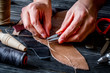 work in leather shop on dark wooden background close up